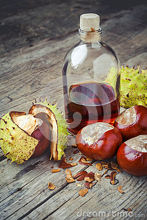 Free Chestnuts And Bottle With Tincture On Wooden Table Stock Photo - 45763870