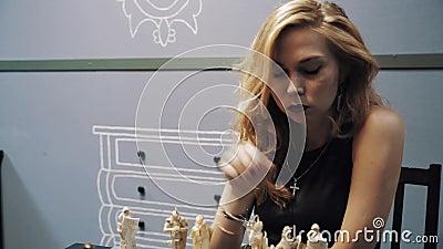Cheveux attrayants blonds de caresse de femme devant la table d'échecs, promenades loin banque de vidéos