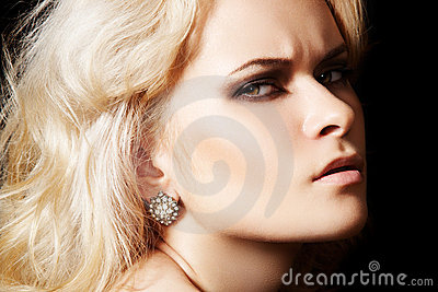 Chic frown model with diamond jewelry, blond hair