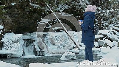 Chica con abrigo azul parada con una taza sobre un fondo de cascada helada y rocas en un bosque de coníferas cubierto de nieve In almacen de metraje de vídeo