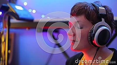 Chica con auriculares tocando un instrumento musical almacen de video
