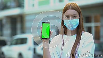 Chica con mascarilla enferma sosteniendo un teléfono de pantalla verde, cita con el médico en línea metrajes