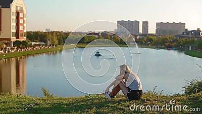 Chica delgada sentada en la colina y mira la belleza del asombroso paisaje pictórico de la ciudad de estilo europeo con edificios almacen de video