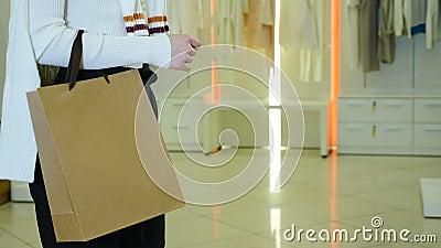 Chica elegante irreconocible con bolsa de papel blanco y marrón con espacio de copia 4.000 imágenes en la compra almacen de video