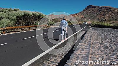 Chica en una chaqueta de denim y pantalones a rayas va a la distancia a lo largo de un camino de asfalto en las tierras altas almacen de metraje de vídeo