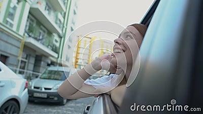 Chica feliz mirando la ventana y disfrutando de las atracciones de la ciudad viajando en auto almacen de video