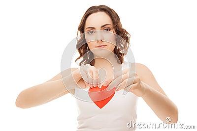 Chica joven atractiva que lleva a cabo el corazón rojo de papel roto de la tarjeta del día de San Valentín