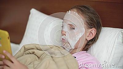 Chica joven con la máscara de los cosméticos del paño en la cara de la piel que miente en malo Muchacha del adolescente que usa s almacen de metraje de vídeo