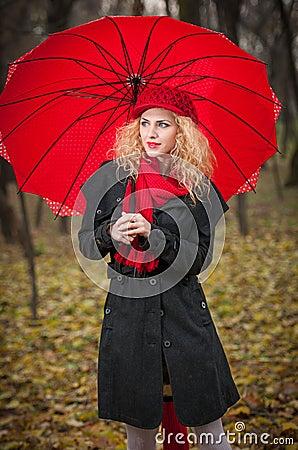 Chica joven de moda hermosa con el paraguas rojo, el casquillo rojo y la bufanda roja en el parque