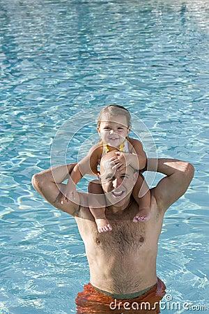 Chica joven en hombros del padre en piscina