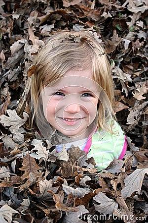 Chica joven en pila de la hoja