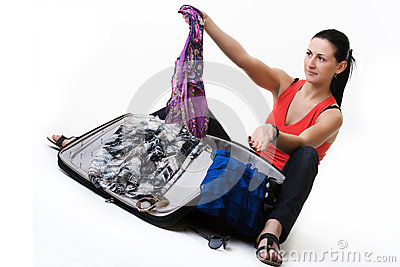 Mujer joven que prepara su equipaje antes de viaje