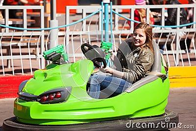 Chica joven que conduce un coche de parachoques