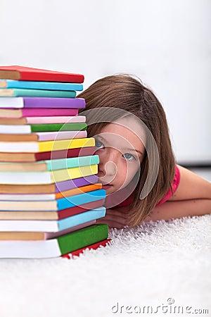 Chica joven que oculta detrás de los libros