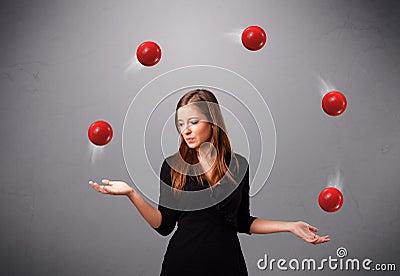 Chica joven que se coloca y que hace juegos malabares con las bolas rojas