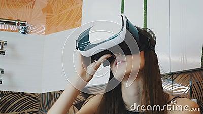 Chica joven que se sienta en cuarto de baño en vidrios de la realidad virtual en la cabeza Mirada para arriba almacen de video