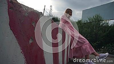 Chica vestida de rosa sentada en un bloque de hormigón, un cartel vacío en el fondo almacen de metraje de vídeo