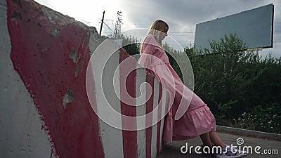 Chica vestida de rosa sentada en un bloque de hormigón, un cartel vacío en el fondo almacen de video