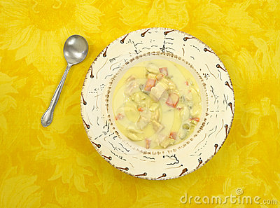 Chicken dumpling soup on yellow tablecloth