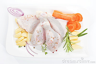 Chicken legs with vegetables on white tray.