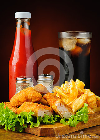 Chicken nuggets, french fries, cola and ketchup