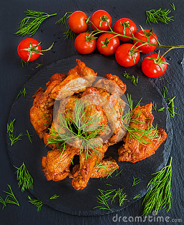 Free Chicken Wings Cooked With Barbecue Sauce On Black Stone Background. Small Cherry Tomatoes And Dill. Top View Stock Images - 73721924