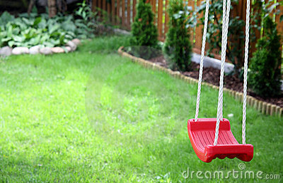 child's swing on green grass