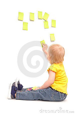 Child of 2 years old sticks paper sheets