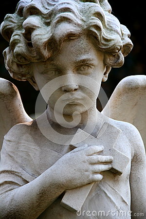 Tombstone with child angel holding a cross on cemetery in Rome.