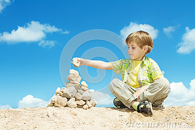 Child ans stones over blue sky