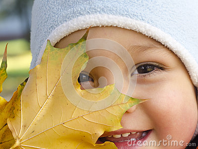 Child with autumn leaf