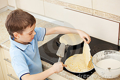 Child bakes pancakes at home