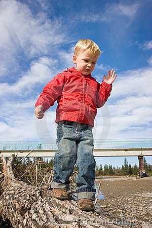 Child balancing on log