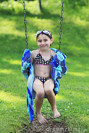 Child in bathing suit on swing