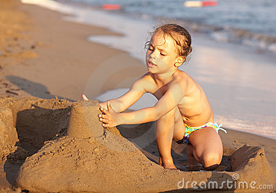 Child on the beach playing with sand.