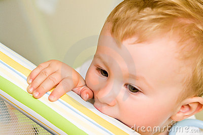 Child biting playpen rail
