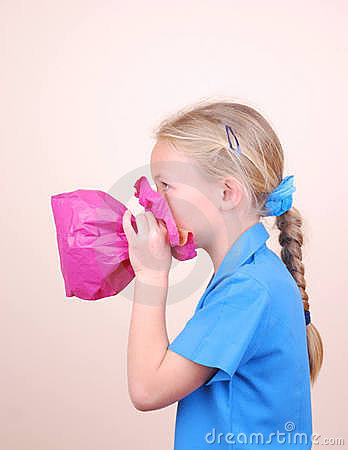 Child blowing pink paper bag