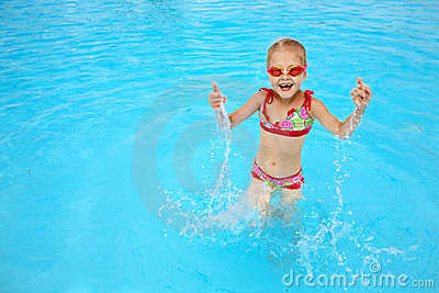 Child in blue water of the swimming pool