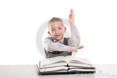 Child with books at desk gesturing hand up for answering school