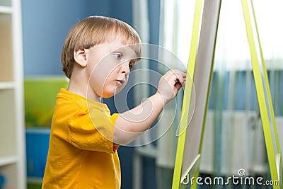 Child boy chalk drawing on blackboard Stock Photo