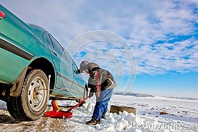 Child boy helps repairing car
