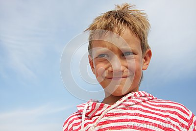 Child boy making faces over sky background