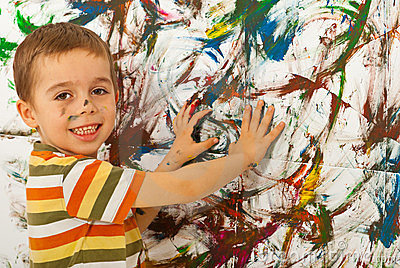Child boy painting wall with hands