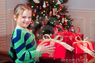 Child bringing Christmas presents with tree