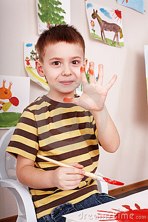 Child with brush draw red sun in play room.