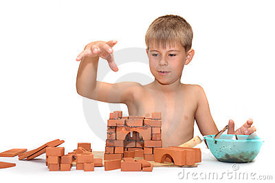 Child build a small house made ​​of bricks