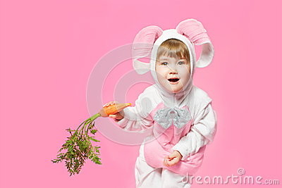 Child in bunny hare costume holding carrots.