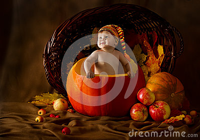 Child in cap inside pumpkin. Autumn harvest