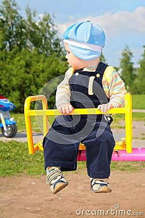 Child on carousel and watch ot motorbike