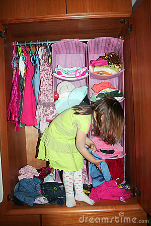 Child choosing dress in her wardrobe